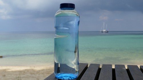 beach sea water light sky sun warm lake summer boot holiday drink bottle blue glass bottle mineral water farbenspiel clouds background vision bright water bottle thirst mood bottle caps sailing boat mirroring longing bluish drinking water bottled water