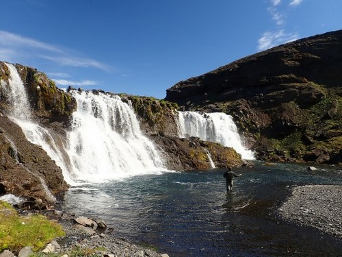Fly fishing in Iceland under a waterfall