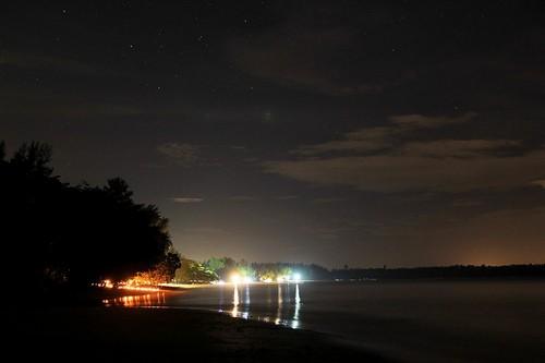 Ночь, небо, облака, звёзды, огни причала и свечи для романтического свидания на берегу ночного моря. Пляж White Sands Beach в Khao Lak, Таиланд